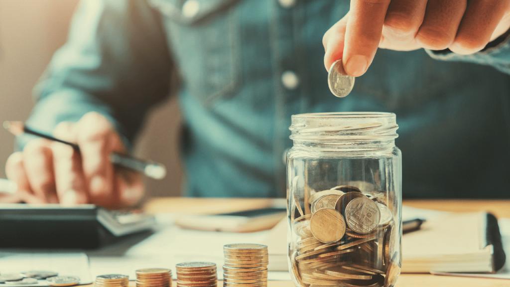 a businessman puts coins in a glass jar