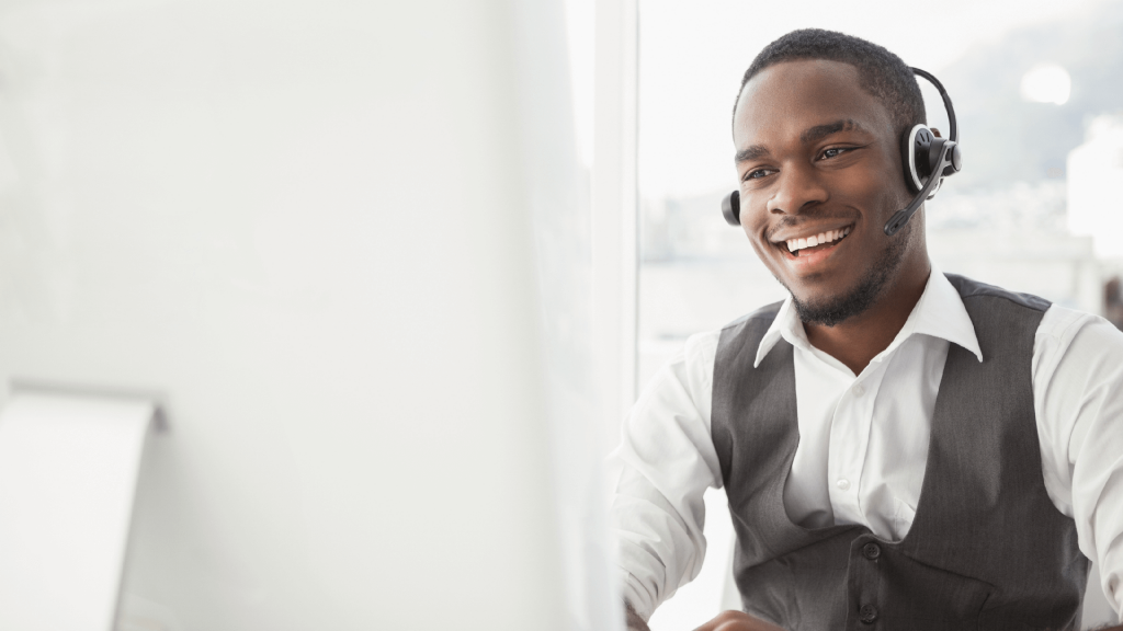 a smiling businessman talks on a headset