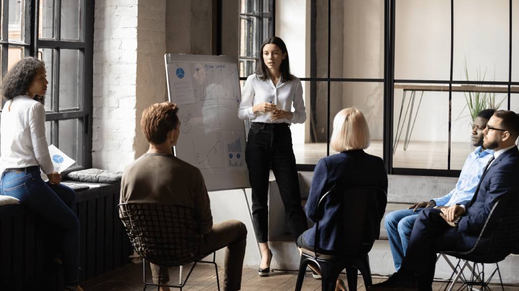 a woman coaches a team of business people