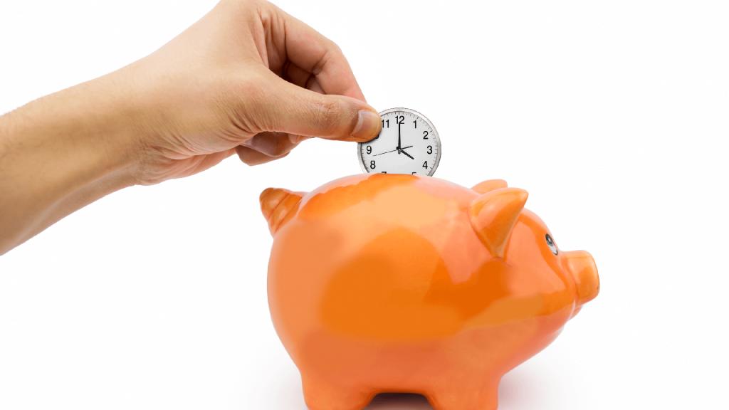 a hands puts a clock in a piggy bank
